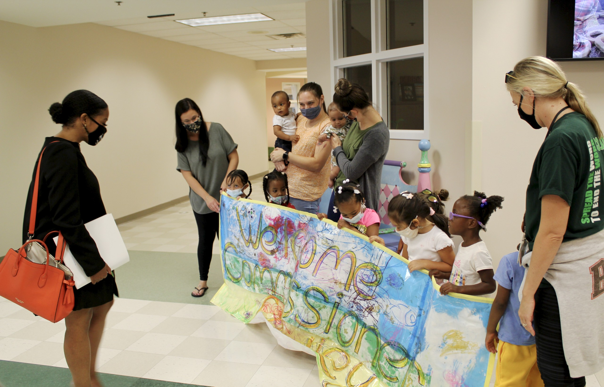Children holding welcome banner for Commissioner Crawley